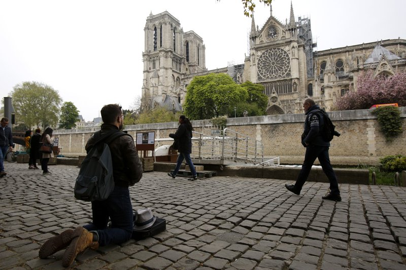 Man kneels as people came to watch and photograph the Notre Dame cathedral after the fire in Paris, Tuesday, April 16, 2019. (AP Photo/Christophe Ena)