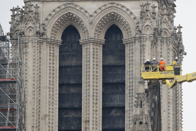 A crane lifts experts as they inspect the damaged Notre Dame cathedral after the fire in Paris, Tuesday, April 16, 2019. (AP Photo/Christophe Ena)