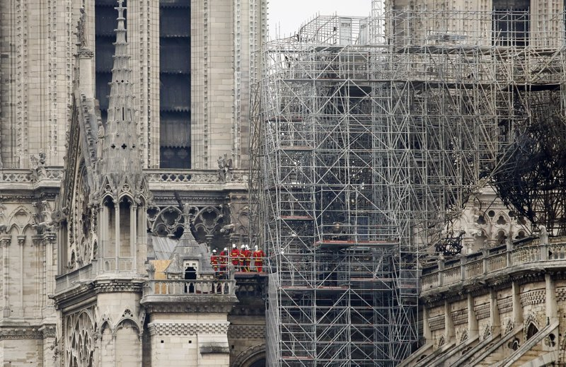 Firemen inspect the Notre Dame cathedral after the fire in Paris, Tuesday, April 16, 2019. Experts are assessing the blackened shell of Paris' iconic Notre Dame cathedral to establish next steps to save what remains after a devastating fire destroyed much of the almost 900-year-old building. (AP Photo/Christophe Ena)