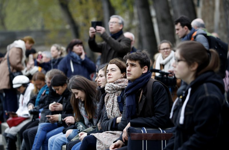 People watch and photograph the Notre Dame cathedral after the fire in Paris, Tuesday, April 16, 2019. (AP Photo/Christophe Ena)