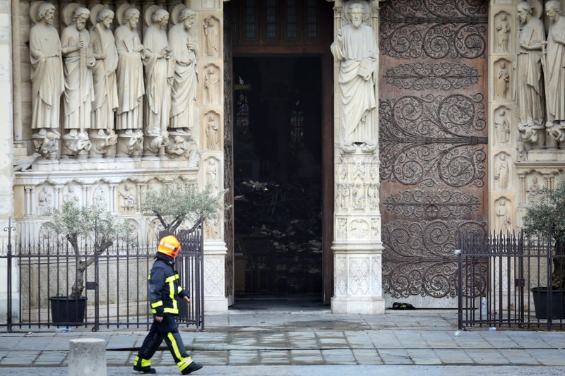 A firefighter walks in front of Notre Dame cathedral Tuesday April 16, 2019 in Paris. Firefighters declared success Tuesday morning in an over 12-hour battle to extinguish an inferno engulfing Paris' iconic Notre Dame cathedral that claimed its spire and roof, but spared its bell towers. (Ludovic Marin via AP)