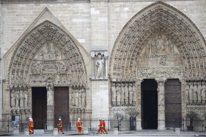 Firefighters walk outside the main entrances of Notre Dame cathedral Tuesday April 16, 2019 in Paris. (AP Photo/Francois Mori)