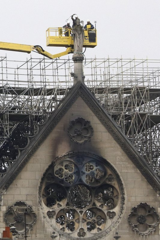 Experts prepare to lift a statue from the damaged Notre Dame cathedral after the fire in Paris, Tuesday, April 16, 2019. (AP Photo/Kamil Zihnioglu)