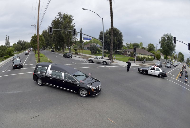 The hearse carrying the body of California Highway Patrol Sgt. Steve Licon makes its way through the intersection of Madison Street and Magnolia Avenue in Riverside, Calif. (Will Lester/The Orange County Register via AP)