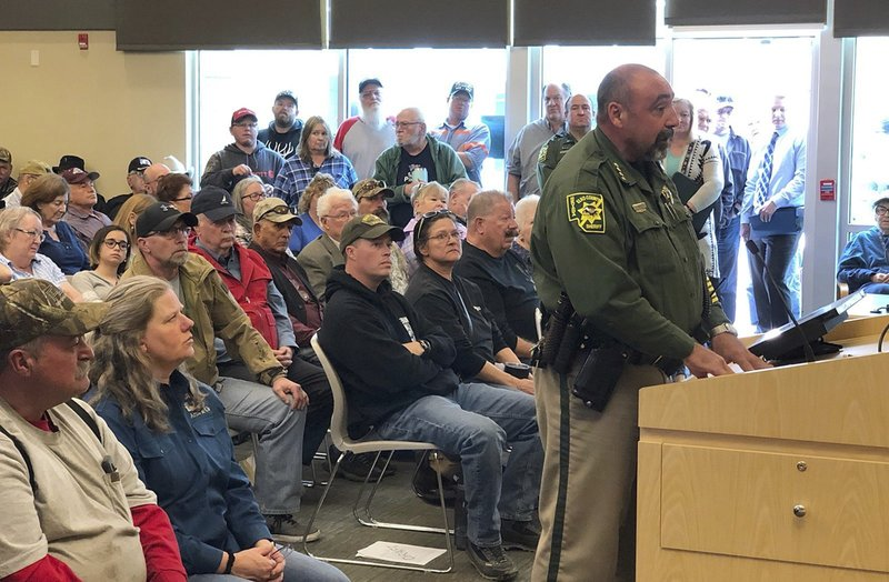 FILE - In this Wednesday, March 20, 2019, file photo, An overflowing crowd packs the Elko County Commission chamber as Elko County Sheriff Aitor Narvaiza presents his case for the county to declare a