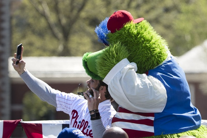 Philadelphia Phillies' Bryce Harper makes a selfie with the team mascot, the Phillie Phanatic, during a Major League Baseball news conference, Tuesday, April 16, 2019, on Independence Mall in Philadelphia. (AP Photo/Matt Rourke)