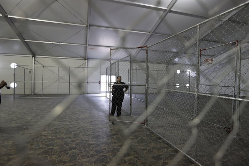 FILE--In this Dec. 7, 2016 file photo, a U.S. Customs and Border Protection agent stands in a temporary holding facility near the Donna-Rio Bravo International Bridge in Donna, Texas. (AP Photo/Eric Gay, File)