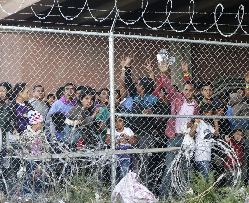 FILE--In this March 27, 2019, file photo, Central American migrants wait for food in a pen erected by U. (AP Photo/Cedar Attanasio, File)