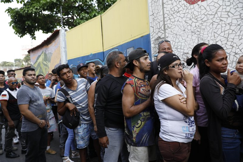 People wait to be given empty water containers and water purification pills during the International Red Cross' first aid shipment in Caracas, Venezuela, Tuesday, April 16, 2019. (AP Photo/Ariana Cubillos)