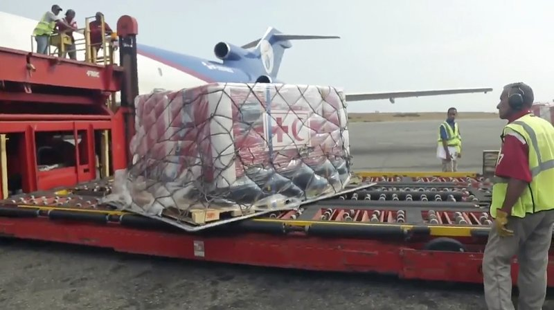 In this image taken from video provided by the International Red Cross, airport employees unload the first shipment of humanitarian aid from the International Federation of Red Cross and Red Crescent Societies at the Simon Bolivar International Airport in Maiquetia, Venezuela, Tuesday, April 16, 2019. (International Committee of the Red Cross via AP)