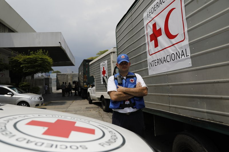 A convoy of trucks arrive at a warehouse transporting from the international airport the first shipment International Federation of Red Cross and Red Crescent Societies humanitarian aid, in Caracas, Venezuela, Tuesday, April 16, 2019. (AP Photo/Ariana Cubillos)