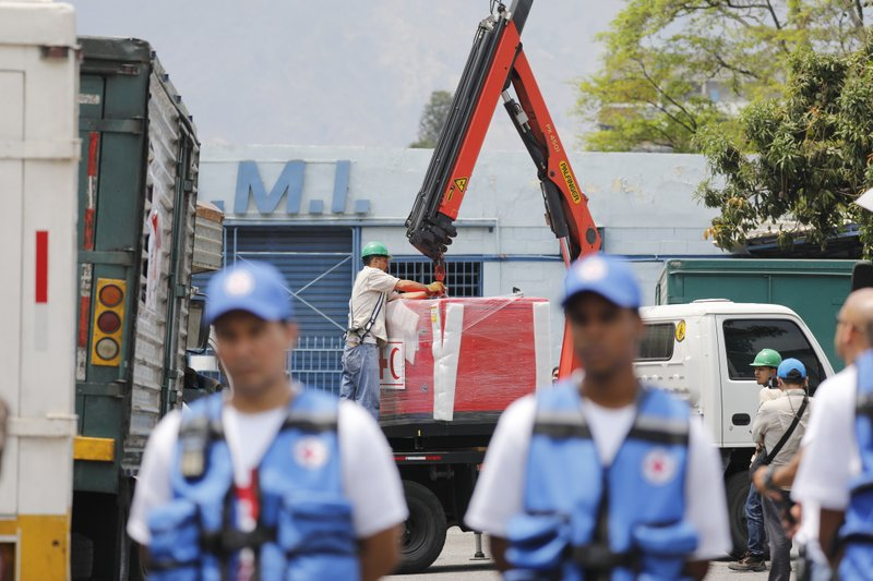 Workers unload the first shipment of humanitarian aid from the International Federation of Red Cross and Red Crescent Societies, at a warehouse in Caracas, Venezuela, Tuesday, April 16, 2019. (AP Photo/Ariana Cubillos)