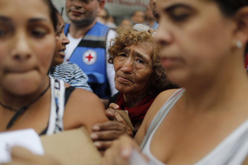 People wait to be given empty water containers and water purification pills during the first aid shipment from the International Red Cross in Caracas, Venezuela, Tuesday, April 16, 2019. (AP Photo/Ariana Cubillos)
