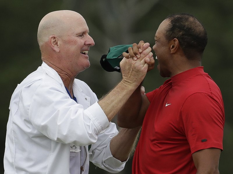 Tiger Woods reacts with his caddie Joe LaCava as he wins the Masters golf tournament Sunday, April 14, 2019, in Augusta, Ga. (AP Photo/Chris Carlson)