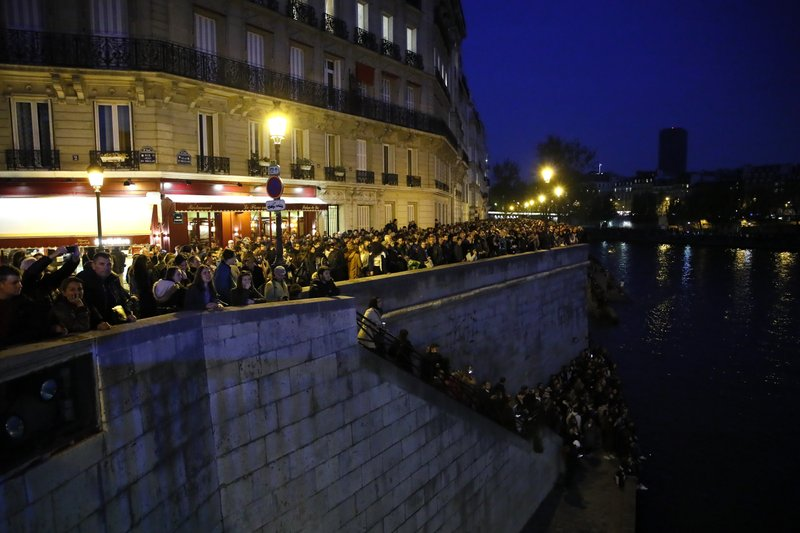 People watch Notre Dame cathedral burning from the Seine river banks in Paris, Monday, April 15, 2019. (AP Photo/Francois Mori)