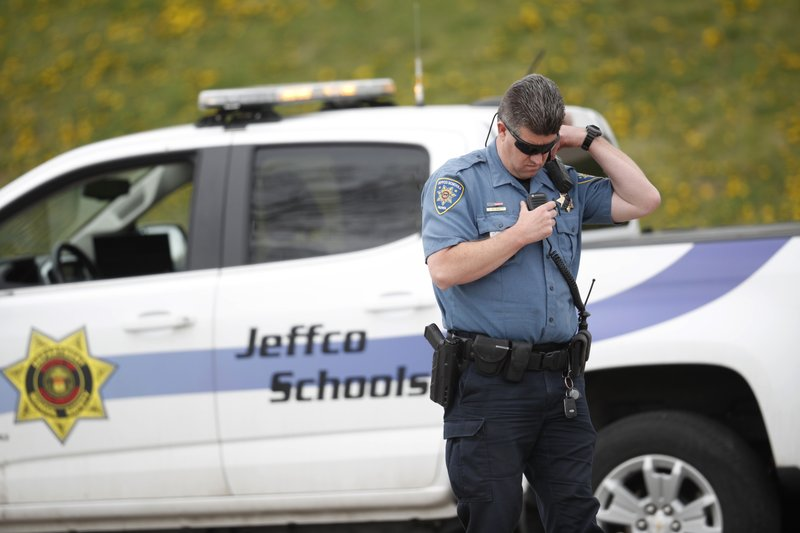 An officer from Jefferson County, Colo., Schools listens on his radio as students leave Columbine High School late Tuesday, April 16, 2019, in Littleton, Colo. (AP Photo/David Zalubowski)
