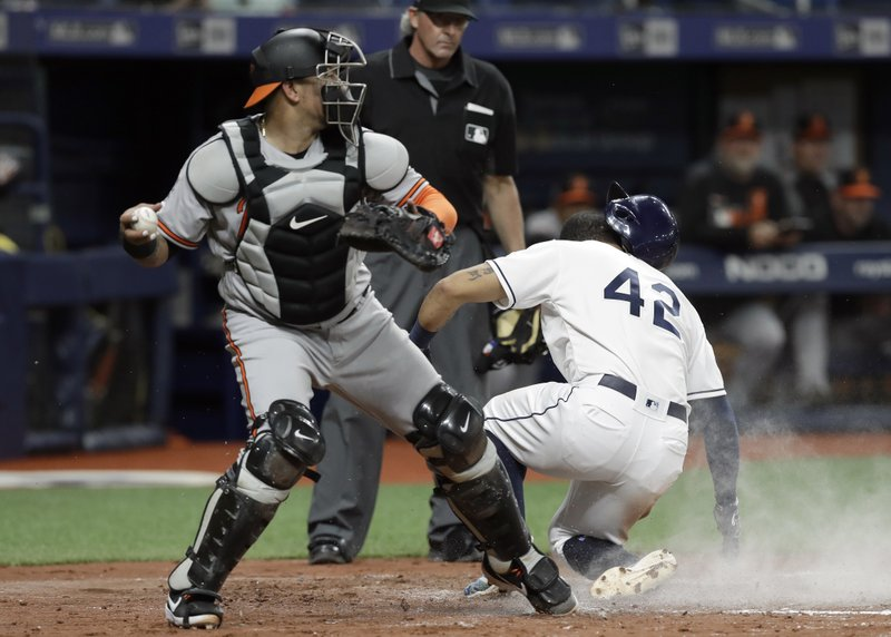 Baltimore Orioles catcher Jesus Sucre, left, looks to throw after Tampa Bay Rays' Tommy Pham scored on a sacrifice fly by Yandy Diaz during the fourth inning of a baseball game Tuesday, April 16, 2019, in St. (AP Photo/Chris O'Meara)