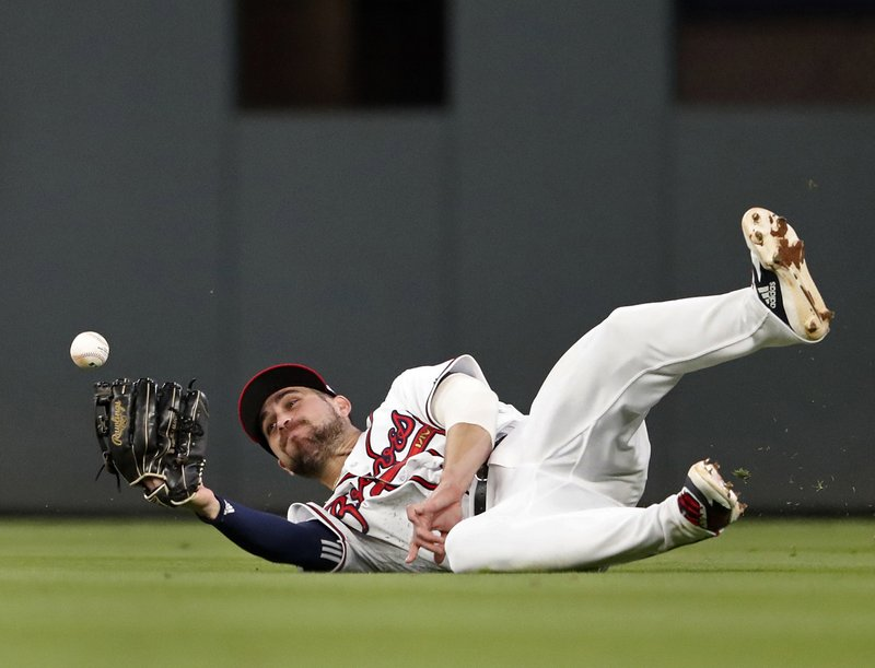 A ball hit for an RBI-single by Arizona Diamondbacks' Nick Ahmed gets away from Atlanta Braves center fielder Ender Inciarte (11) in the fourth inning of a baseball game, Tuesday, April 16, 2019, in Atlanta. (AP Photo/John Bazemore)