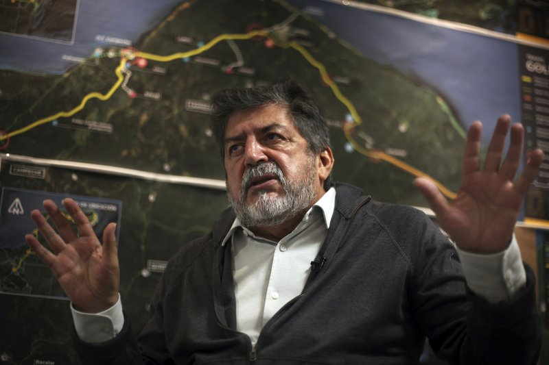 Rogelio Jiménez Pons, director of Fonatur, gives an interview in front of a map of a planned train line through the Yucatan Peninsula, in Mexico City, Monday, March 18, 2019. (AP Photo/Marco Ugarte)