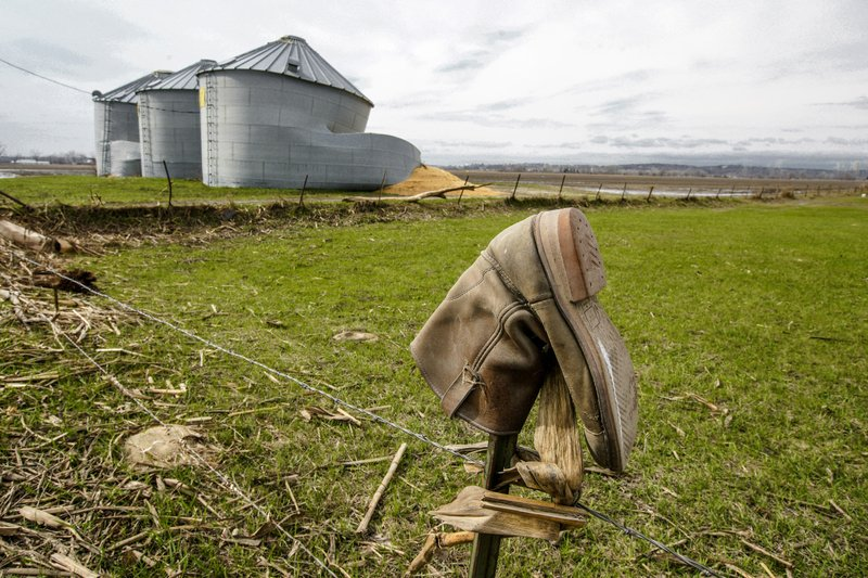 In this Wednesday, April 10, 2019 photo, destroyed grain silos, a result of flooding, spill corn onto a muddy field, are seen on a farm in Bellevue, Neb. (AP Photo/Nati Harnik)