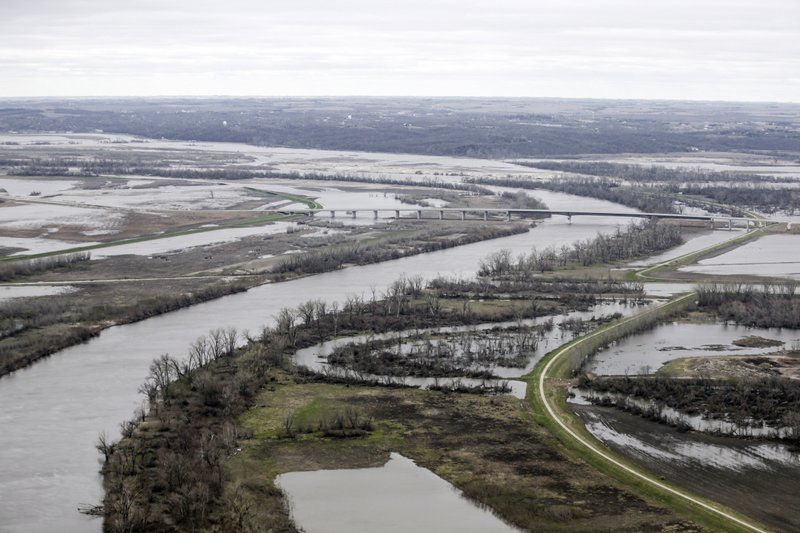 In this Friday, April 12, 2019 photo, the highway 34 bridge spans the Missouri River and it's flooded banks between La Platte, Nebraska and Glenwood, Iowa. (AP Photo/Nati Harnik)