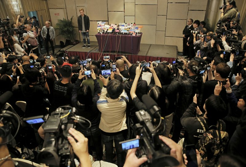 Hong Kong singer Andy Hui stands and let photographers take pictures before a press conference about his affair in Hong Kong, Tuesday, April 16, 2019. (AP Photo/Vincent Yu)