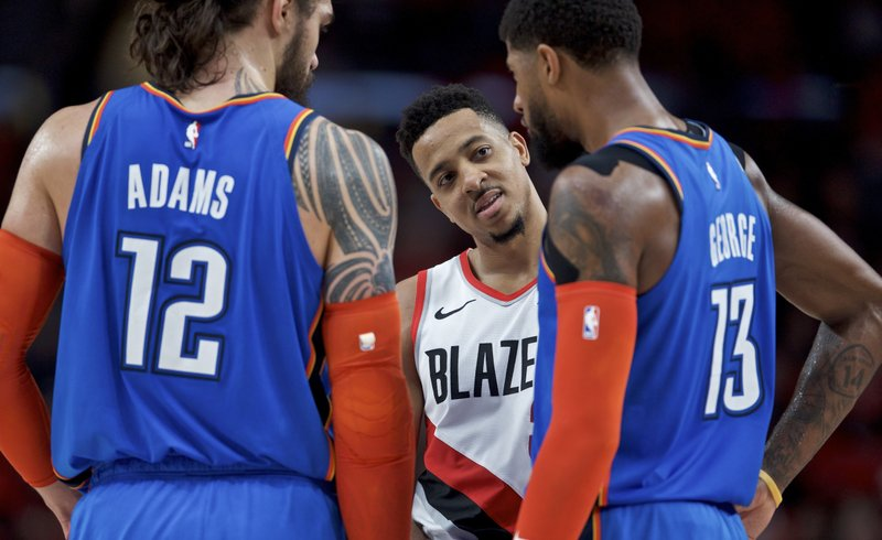 Portland Trail Blazers guard CJ McCollum, center, talks to Oklahoma City Thunder forward Paul George, right, and center Steven Adams during the first half of Game 2 of an NBA basketball first-round playoff series Tuesday, April 16, 2019, in Portland, Ore. (AP Photo/Craig Mitchelldyer)