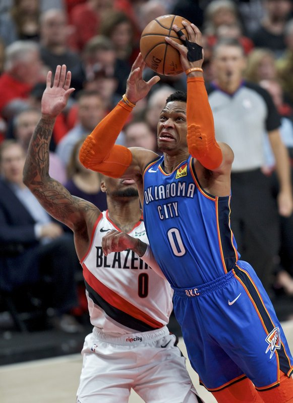 Oklahoma City Thunder guard Russell Westbrook, right, shoots next to Portland Trail Blazers guard Damian Lillard during the first half of Game 2 of an NBA basketball first-round playoff series Tuesday, April 16, 2019, in Portland, Ore. (AP Photo/Craig Mitchelldyer)