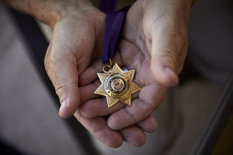 In this April 9, 2019, photo, Grant Whitus holds the Jefferson County Sheriff's Star at his home in Lake Havasu City, Ariz. (AP Photo/John Locher)