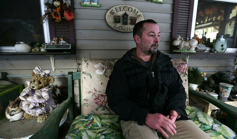 In this Thursday, March 7, 2019 photo, former SWAT officer Al Joyce sits on the porch at his mother's home in Otisfield, Maine. (AP Photo/Robert F. Bukaty)