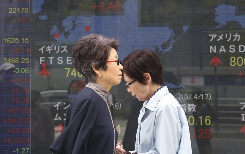People walk by an electronic stock board of a securities firm in Tokyo, Wednesday, April 17, 2019. Shares were mixed in a narrow range Wednesday as China announced its economy grew at a 6. (AP Photo/Koji Sasahara)