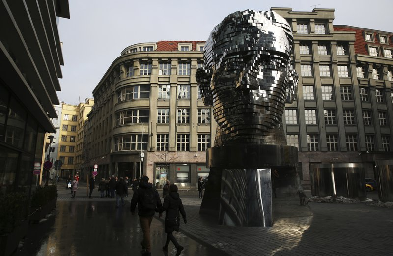 FILE -  In this Feb. 4, 2017 file photo, tourists walk past a moving metal sculpture of writer Franz Kafka in his birth city of Prague, Czech Republic, on Saturday, Feb. (AP Photo/Jon Gambrell, File)