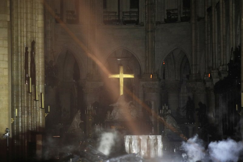Smoke is seen around the alter inside Notre Dame cathedral in Paris, Monday, April 15, 2019. A catastrophic fire engulfed the upper reaches of Paris' soaring Notre Dame Cathedral as it was undergoing renovations Monday, threatening one of the greatest architectural treasures of the Western world as tourists and Parisians looked on aghast from the streets below. (Philippe Wojazer/Pool via AP)
