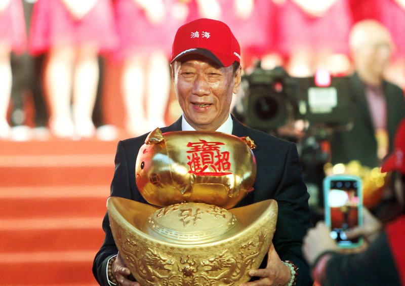 FILE - Terry Gou, chairman of Hon Hai Precision Industry Co. Ltd., also known as Foxconn, holds New Year's lucky charm during the company's annual carnival for employees in Taipei, Taiwan. (AP Photo/Chiang Ying-ying, File)