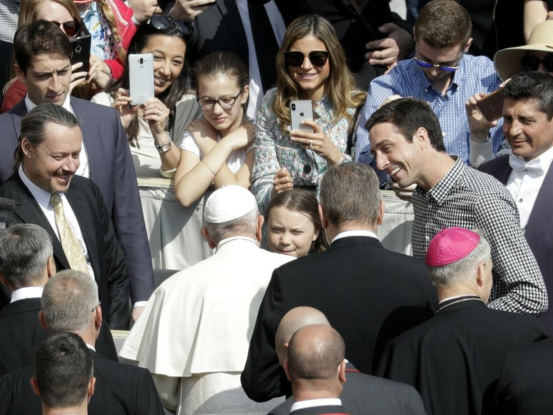 Pope Francis, back to camera, greets Swedish teenage environmental activist Greta Thunberg, center, during his weekly general audience in St. (AP Photo/Gregorio Borgia)