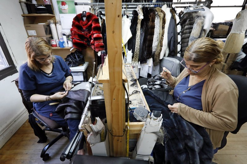 In this April 10, 2019, photo, seamstresses Sonia Genao, left, and Juana Rodrize work on coats at Pologeorgis Furs in New York. (AP Photo/Richard Drew)