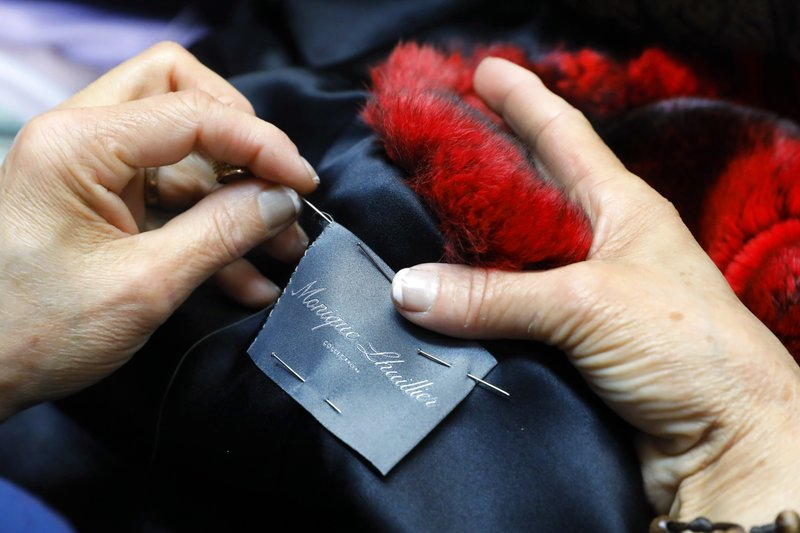 In this April 10, 2019, photo, seamstress Sonia Genao sews a Monique Lhuillier label in a coat at Pologeorgis Furs in New York. (AP Photo/Richard Drew)