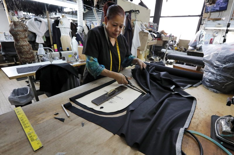 In this April 10, 2019, photo, Maria Rodriguez uses a pattern as she cuts lining for a coat at Pologeorgis Furs in New York. (AP Photo/Richard Drew)
