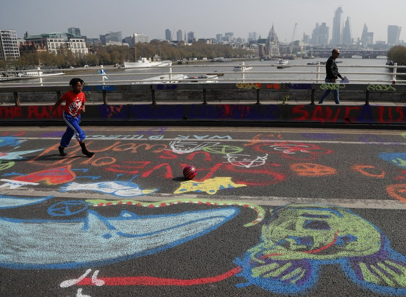 A boy plays football on graffiti drawn by protestors who blocked Waterloo Bridge in London, Wednesday, April 17, 2019, with the River Thames and the city on London in background. (AP Photo/Frank Augstein)