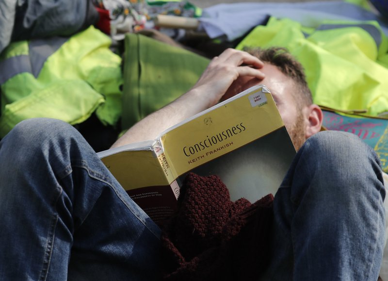 A protestor on Waterloo Bridge reads a book as the road is blocked in London, Wednesday, April 17, 2019. (AP Photo/Frank Augstein)