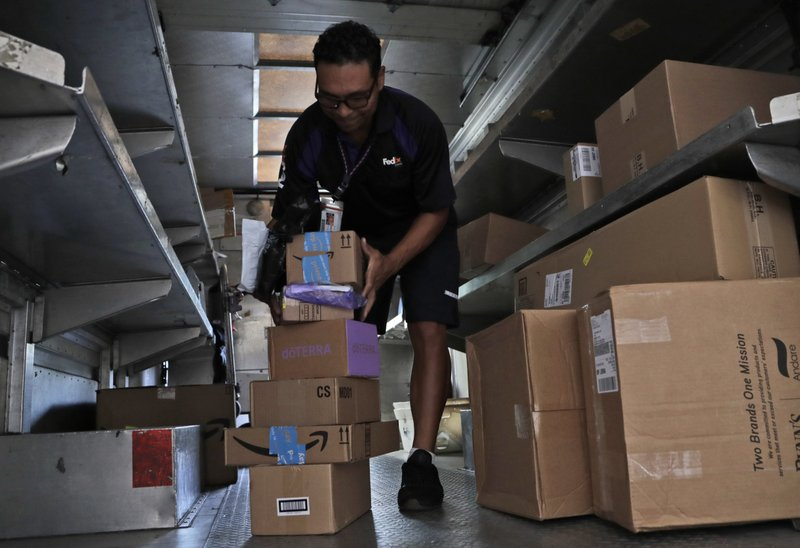 FILE - In this July 17, 2018, file photo, a FedEx employee delivers packages in Miami. Outside of ditching online shopping altogether, there are some small tweaks in how you shop that can cut down on the impact on the environment, such as slowing down shipping times and not filling up the cart with stuff you know you won't keep. (AP Photo/Lynne Sladky, File)