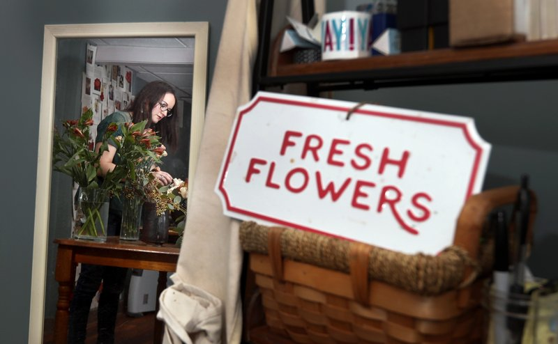 In this April 1, 2019, photo Liz Mally, who owns LPF Blooms, is reflected in a mirror as she works on a centerpiece in her studio in her basement in Ferndale, Mich. (AP Photo/Carlos Osorio)