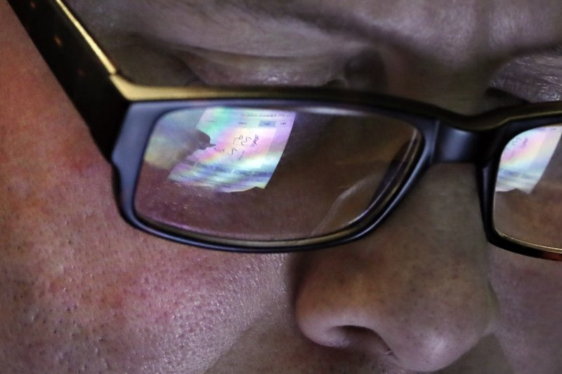 FILE- In this April 11, 2019, file photo trader Jeffrey Vazquez's glasses reflect the screen of his handheld device as he works on the floor of the New York Stock Exchange. (AP Photo/Richard Drew, File)