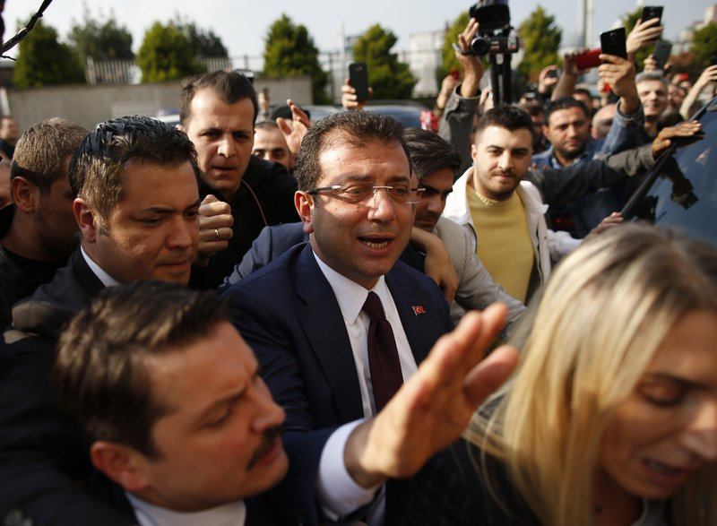 Ekrem Imamoglu, centre, of the opposition Republican People's Party (CHP) mayoral candidate in Istanbul, arrives to receive a certificate confirming his win by a slim margin against ruling party's candidate Binali Yildirim, in Istanbul, Turkey, Wednesday, April 17, 2019. (AP Photo/Emrah Gurel)