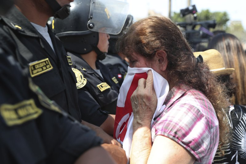 A Supporter of former Peruvian President Alan Garcia cries as she learns that the former leader died from a self-inflicted gun shot, outside the hospital where he was taken after he shot himself, in Lima, Peru, Wednesday, April 17, 2019. (AP Photo/Martin Mejia)