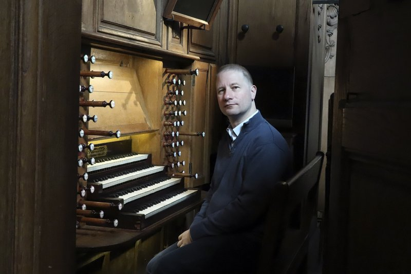 Johann Vexo, the organist who was playing at evening mass inside Notre Dame when flames began licking at the iconic cathedral's roof, poses at the pipe organ at Notre Dame de Nancy cathedral, eastern France, Wednesday, April 17, 2019. (AP Photo/Oleg Cetinic)