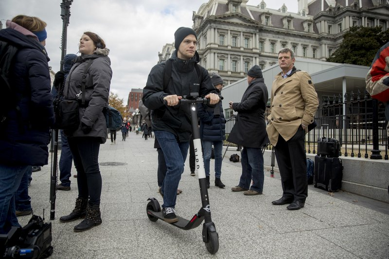In this Dec. 4, 2018, photo a man rides a scooter near the White House in Washington. Electric scooters are overtaking station-based bicycles as the most popular form of shared transportation outside transit and cars. (AP Photo/Andrew Harnik)