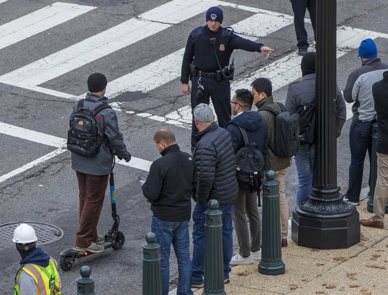 In this Dec. 5, 2018, photo a police officer directs a rider on a Skip brand electric scooter to move off the street on Capitol Hill in Washington. (AP Photo/J. Scott Applewhite)