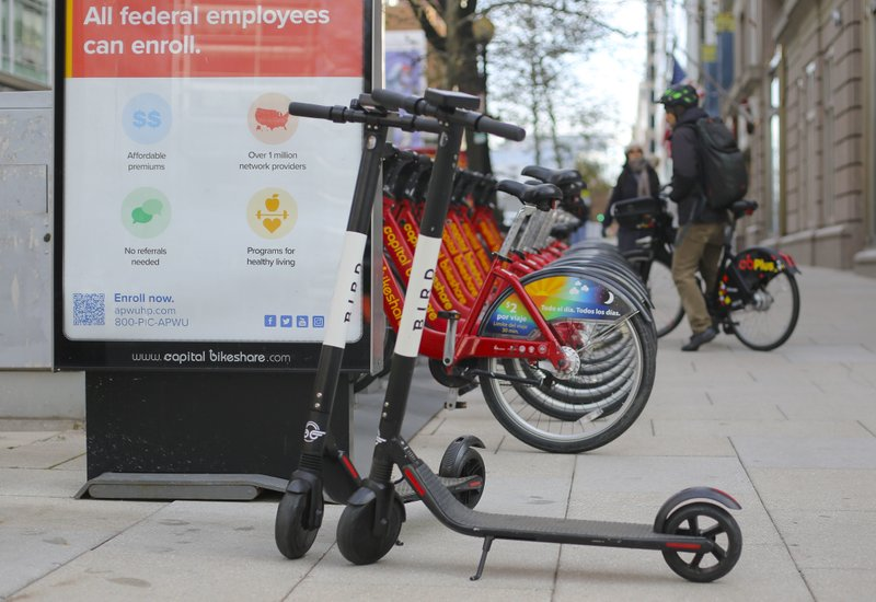 In this Dec. 6, 2018, photo Bird scooters are parked besides a bike sharing docking station in downtown in downtown Washington. (AP Photo/Pablo Martinez Monsivais)