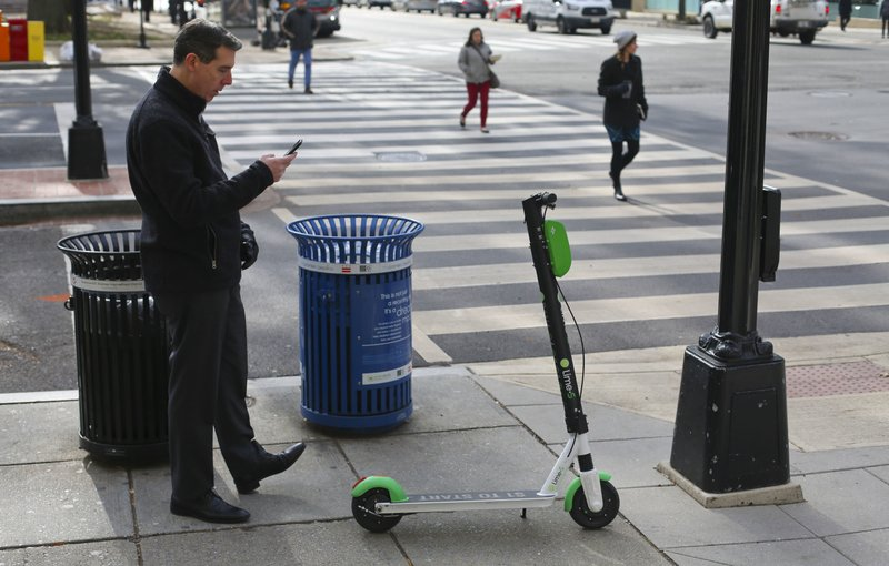 In this Dec. 6, 2018, photo a Lime scooter customer uses his mobile app to lock up his scooter on the sidewalk after finishing his trip in downtown Washington. (AP Photo/Pablo Martinez Monsivais)